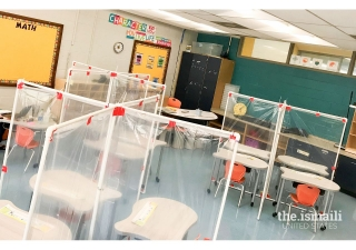 View of a classroom with desk partitions to separate students.