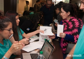 Volunteers provide information to attendees for the Mulaqat events.