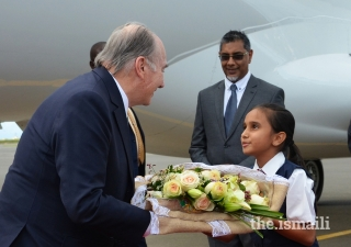 Upon arriving in Nairobi, Mawlana Hazar Imam is presented with a bouquet of flowers by Umaiza Jamal, a young member of the Ismaili Volunteer Corps