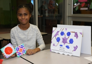 "A young girl displays her geometric shape tile artwork, featuring traditional elements of Islamic art from the Aga Khan Museum publication, ""Astounding ABC."""