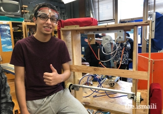 Saif Punjwani standing next to the prototype of his FIRST Robotics Competition team's lift mechanism. Saif led the creation of the lift mechanism, which was a crucial component that allowed his team's 2019 robot to lift above the ground and reach a new level.