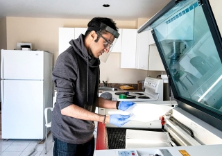 Rahim Bhimani uses the industrial laser cutting machine in his basement to create thousands of face shields for healthcare workers.