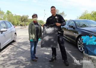 A Milpitas Police officer receives an I-CERV t-shirt from an Ismaili volunteer.