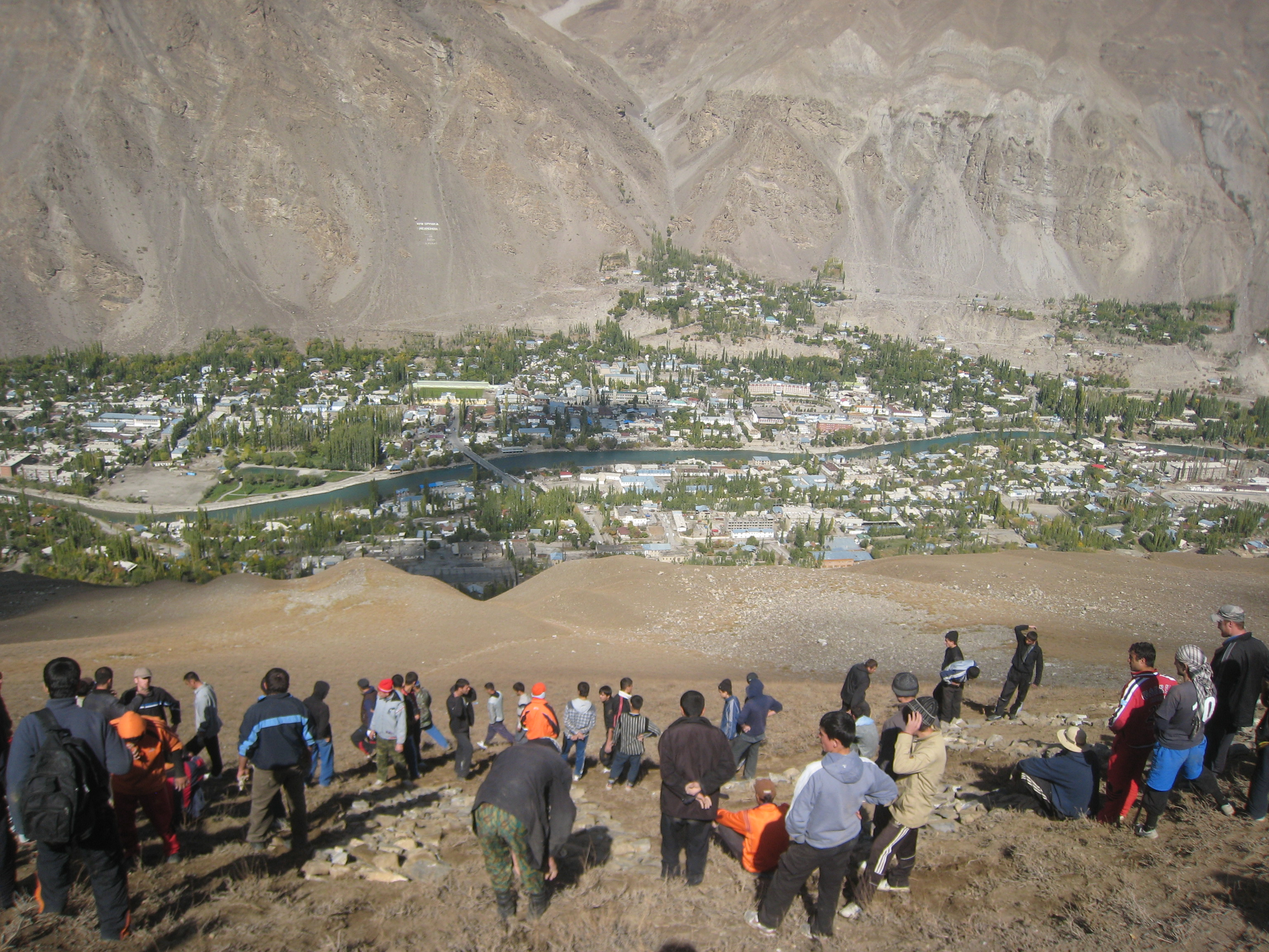 Volunteers move rocks to create a mountain-side Golden Jubilee welcome sign for Mawlana Hazar Imam. The city of Khorog is visible below. Photo: Gordon Cumming
