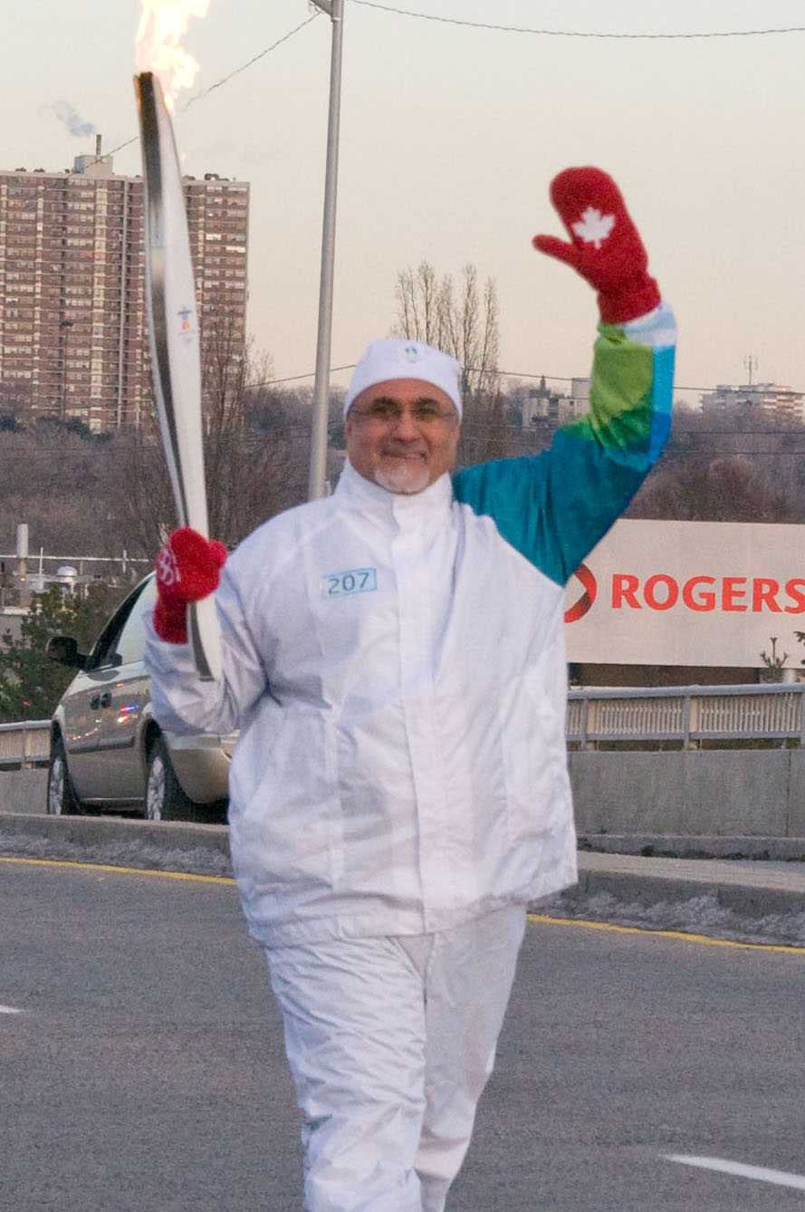 President Manji waves at the residents of Don Mills as he carries the Olympic Torch along York Mills Road in Toronto. Photo: Moez Visram