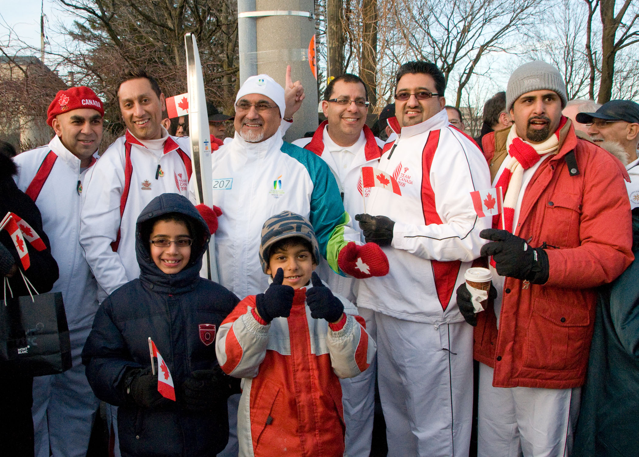 Olympic Torch-Bearer, President Mohamed Manji, is surrounded by athletes who competed in the Canadian Ismaili Games in Vancouver and the Golden Jubilee Games in Nairobi. Held in 2008, both Games emphasised about the pursuit of excellence and unity amongst peoples. Photo: Moez Visram