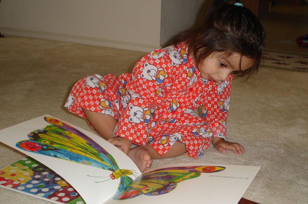 "Aanyah Abdullah is mesmerised by Eric Carle's ""The Very Hungry Caterpillar"". Photo: Shaila Abdullah"