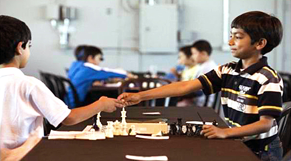 Danial shakes hands with an opponent during a friendly chess competition. Photo: Michael Goulding, Orange County Register