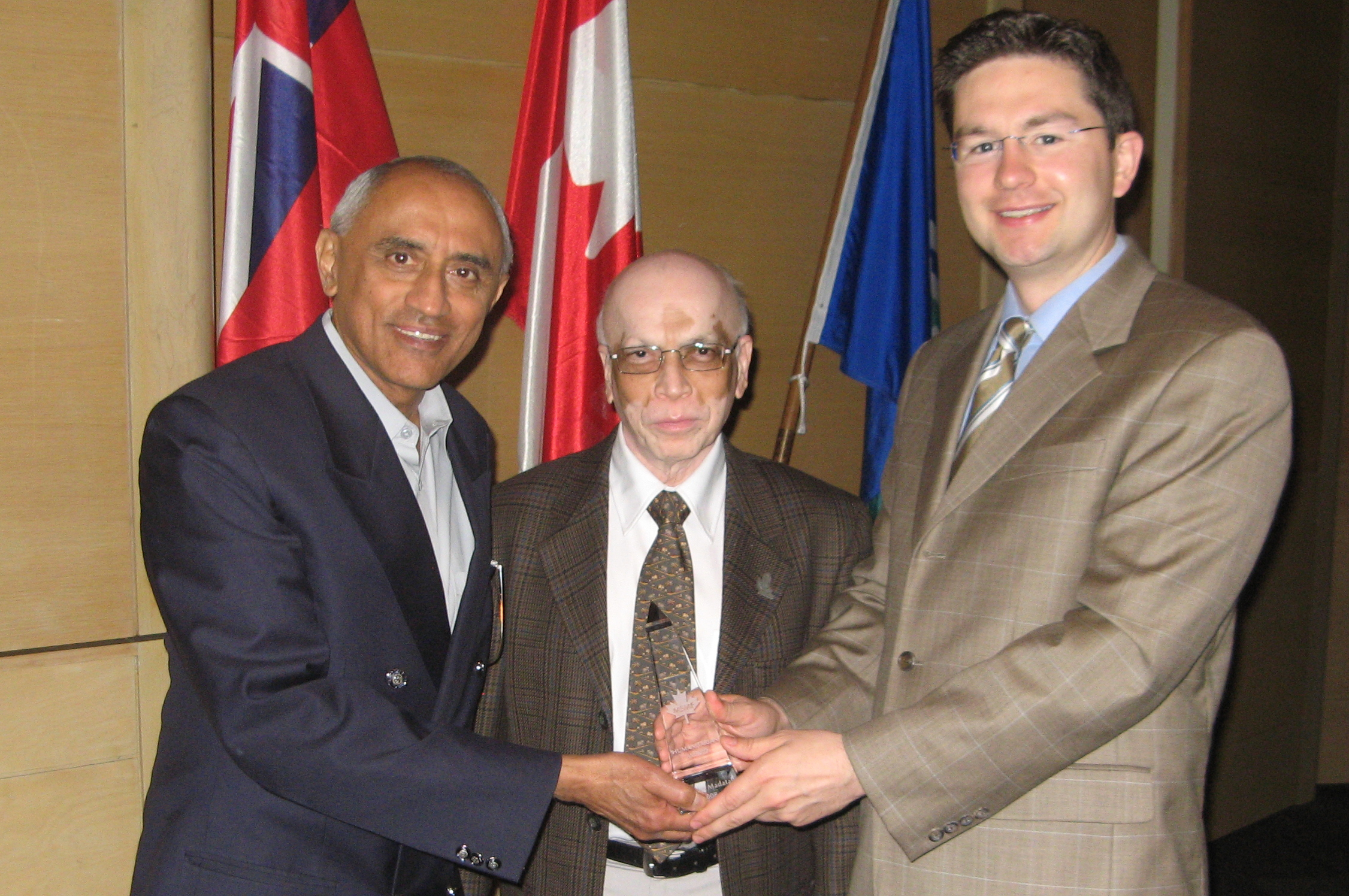 Noordin  Madatali (left) receives the MSMF Humanitarian Award from Dr Chandrasekhar Sankurathri, Founder of MSMF and Canadian Member of Parliament Pierre Poilievre. Photo: Courtesy of Noordin Madatali
