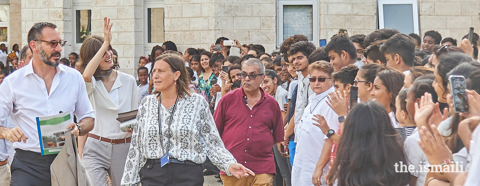 Prince Rahim and Princess Salwa, accompanied by the Head of the Aga Khan Academy Mombasa, Ms Alison Hampshire, wave goodbye to students and parents upon their departure from the school.