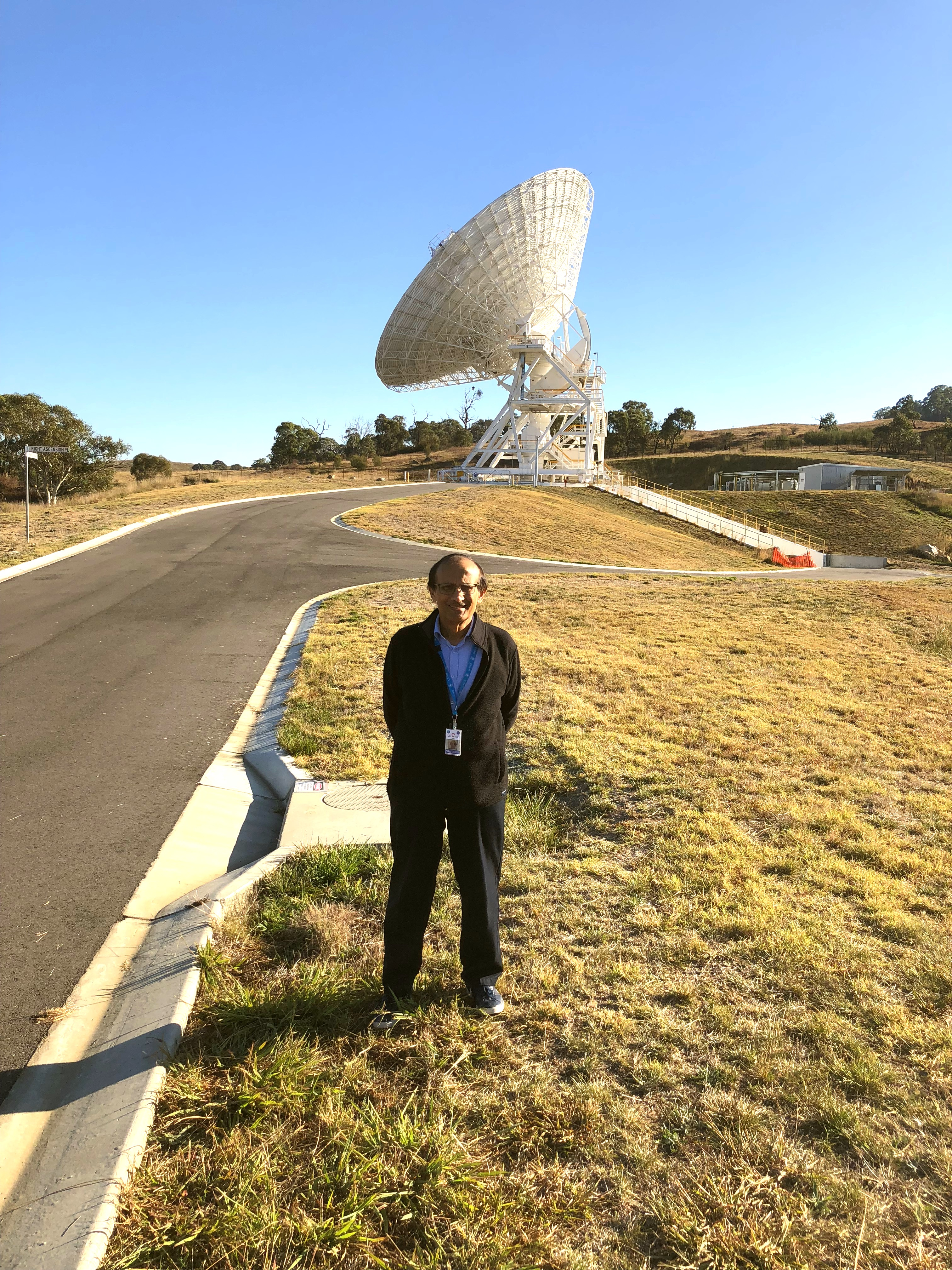 Alaudin Bhanji in front of the newest antenna built under his leadership in Australia.