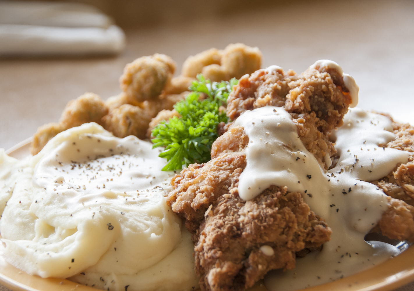 Southern comfort food at its best - mashed potatoes with country fried chicken and gravy on top.