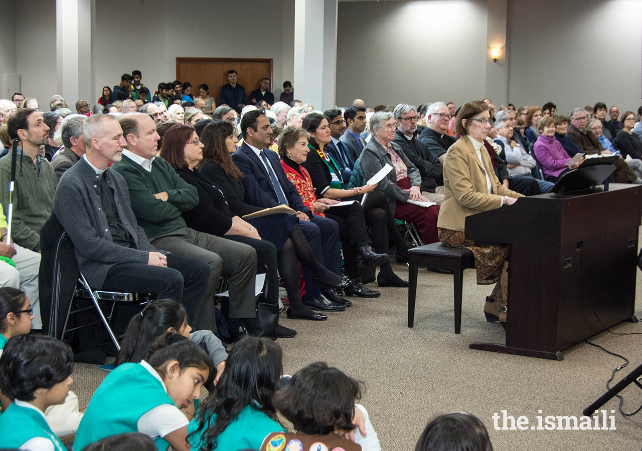 Interfaith leaders and guests of Edgewater Community Religious Association attending the Thanksgiving gathering at the Chicago Jamatkhana Social Hall. The Ismaili Girl Scouts are seated in the front.