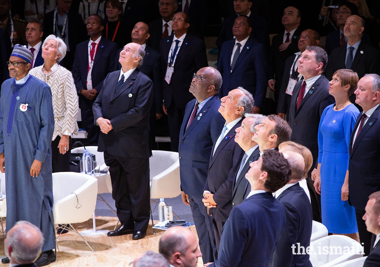 The world leaders gathered for the opening session of the inaugural Paris Peace Forum all look to the sky as an aerial photograph is taken to mark this historic event.