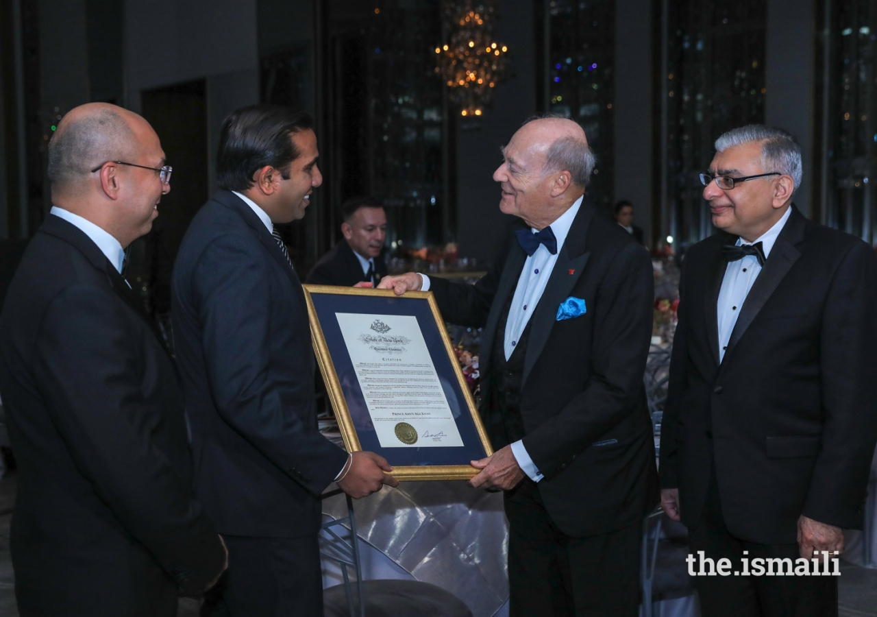 Hersh Parekh, Esq, representing the Office of Governor Andrew M. Cuomo, presents Prince Amyn  with a State of New York Executive Chamber Citation, as Barkat Fazal, President of the Ismaili Council for the USA looks on.