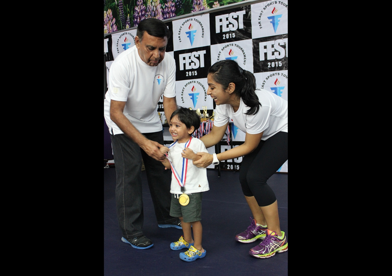 Two-year-old athlete celebrates receiving a medal for his participation at the Far East Sports Tournament.