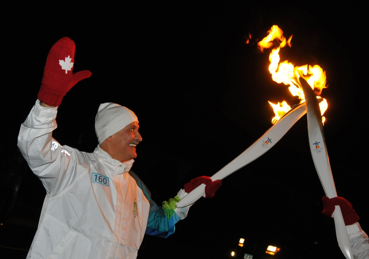 In a kiss of torches, Salim Ahmed receives the Olympic flame in Abbotsford, British Columbia.