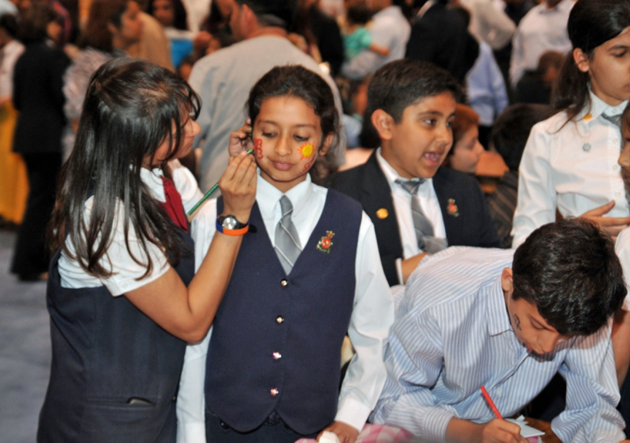 Youth volunteers take a moment to join in the fun and have their faces painted.