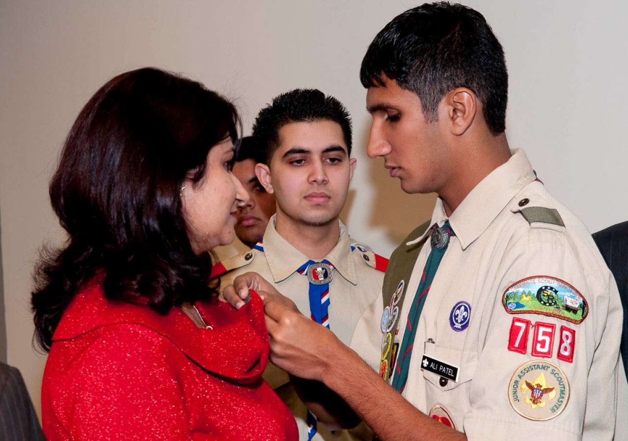 Ali Patel presents his mother with a pin for supporting him throughout his Eagle Scout project. Each of the recipients gave pins to their mothers in appreciation of their support.