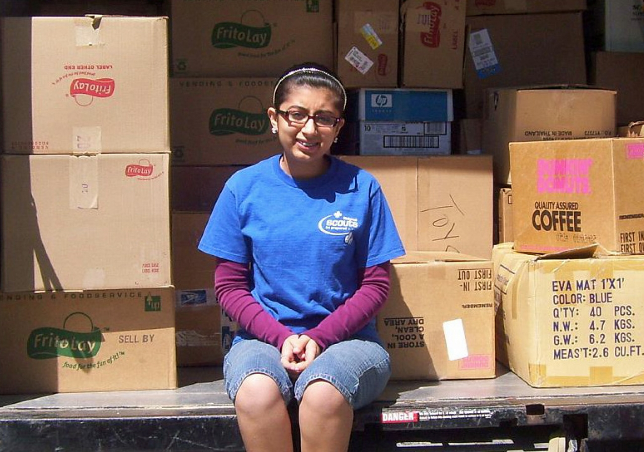 Natasha Tharwani sits among some of the 222 boxes of school supplies collected for donation to RISE International for schools in Angola.