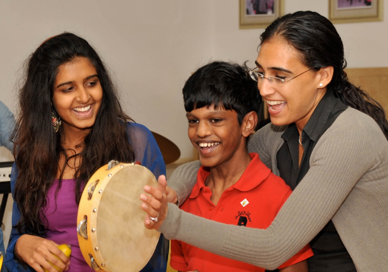 Members of ICE help a young person from Rashid Paediatric Therapy Centre in Dubai to play the tambourine.