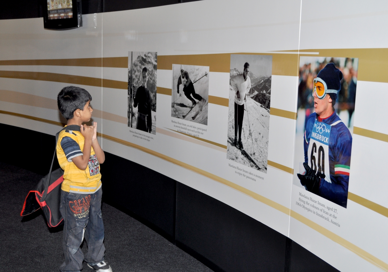 A boy is drawn to photographs of a younger Mawlana Hazar Imam, who skied at the 1964 Winter Olympics in Innsbruck, Austria.