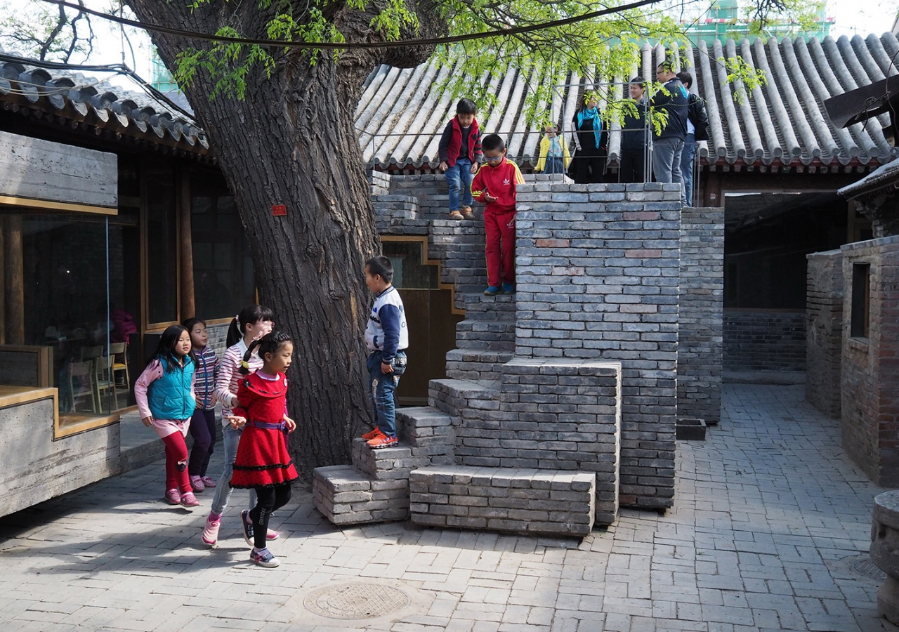 A trail of brick stairs leads up to the roof at the Hutong Children's Library and Art Centre in Beijing, where children delve into the foliage of the big tree. AKTC / Zhang MingMing, ZAO, standardarchitecture