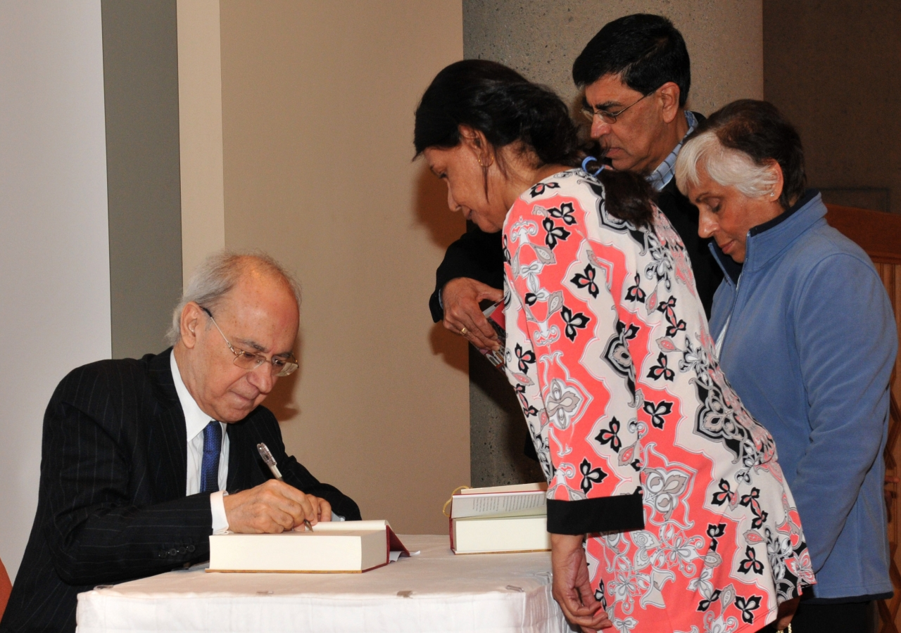 """Dr Farhad Daftary signs copies of the publication """"Fortresses of the Intellect"""" at the Ismaili Centre, Burnaby."""