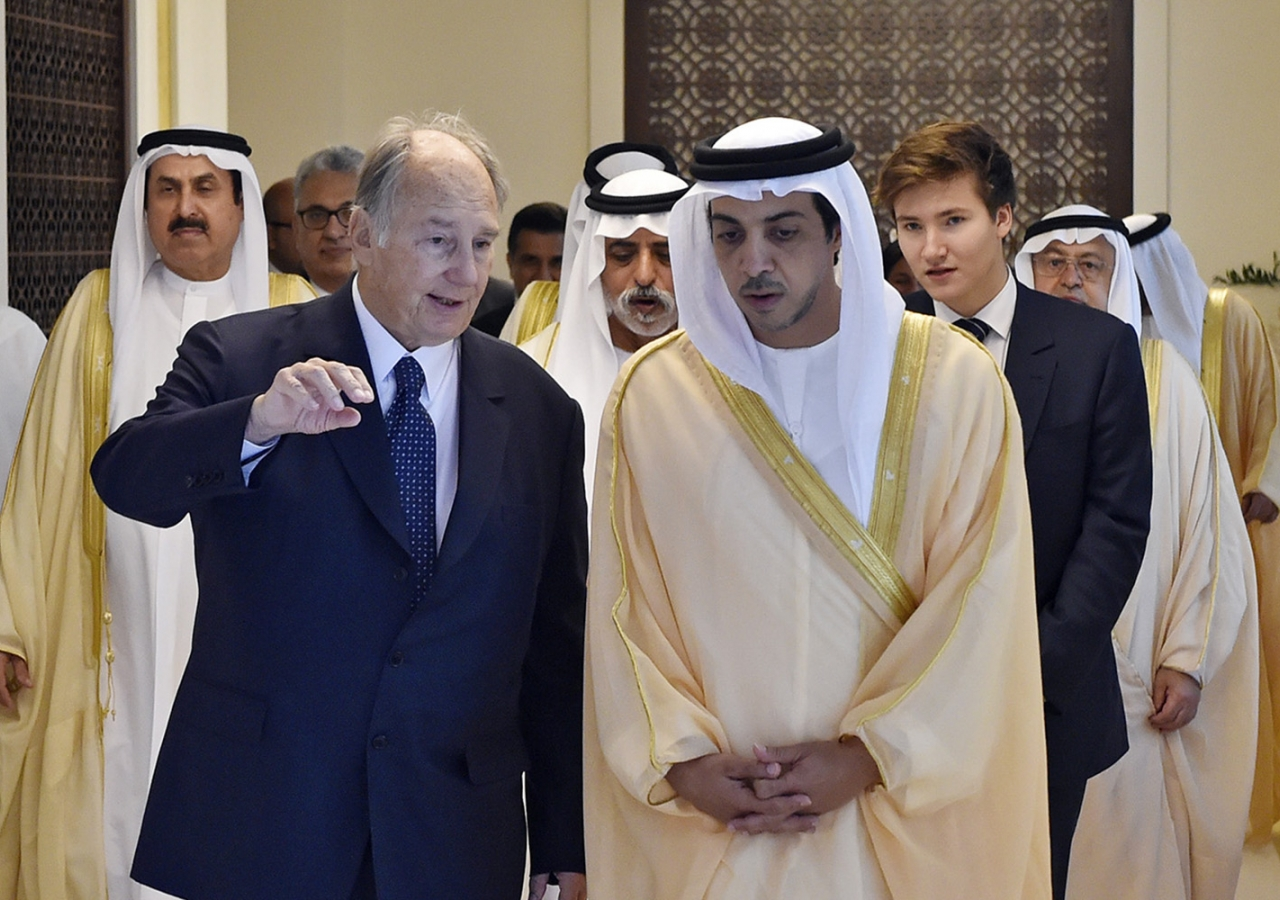 Mawlana Hazar Imam and Sheikh Mansoor engaged in conversation as they walk down a hallway. They are followed by Sheikh Nahyan bin Mubarak Al Nahyan and Prince Aly Muhammad. Gary Otte