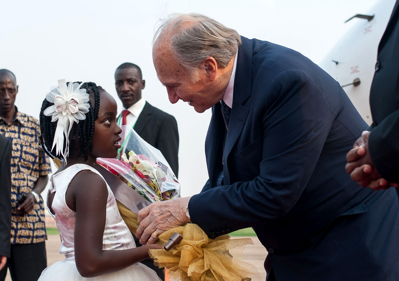 A six-year-old girl presents flowers to Mawlana Hazar Imam as he steps off the plane at Entebbe. AKDN / Will Boase