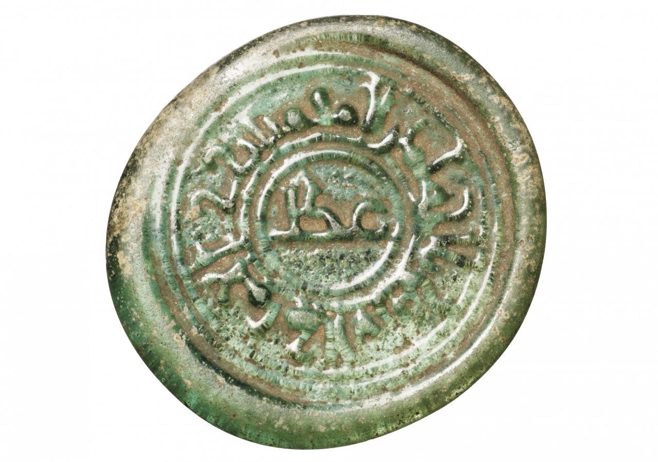 The outer marginal inscription reads al-Imam al-'Aziz bi'llah amir al-mu'minin, and the inner circle contains the word 'adl.