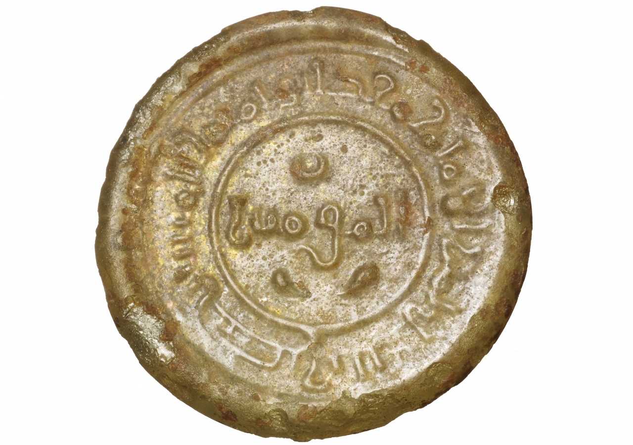 The inscription in the circular plain border, reads al-Imam Ma'ad Abu Tamim al-Mustansir bi'llah amir. The inscription in the center reads, al-mu'minin. On the reverse, a partial date most likely refers to AH 439 (1047-48 CE).