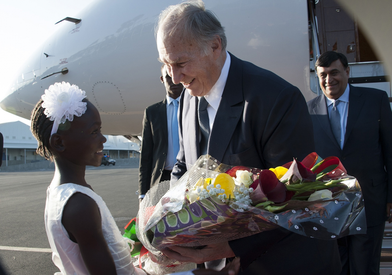 Mawlana Hazar Imam is welcomed by an 8-year-old girl, who presents him with a bouquet upon his arrival in Nairobi. Aziz Islamshah