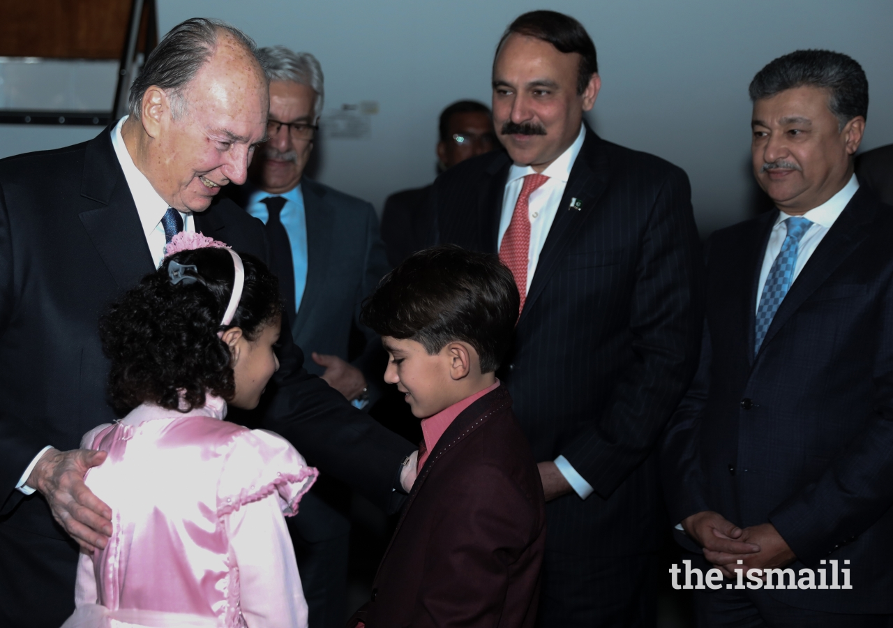 Mawlana Hazar Imam in a light moment with children presenting bouquets.