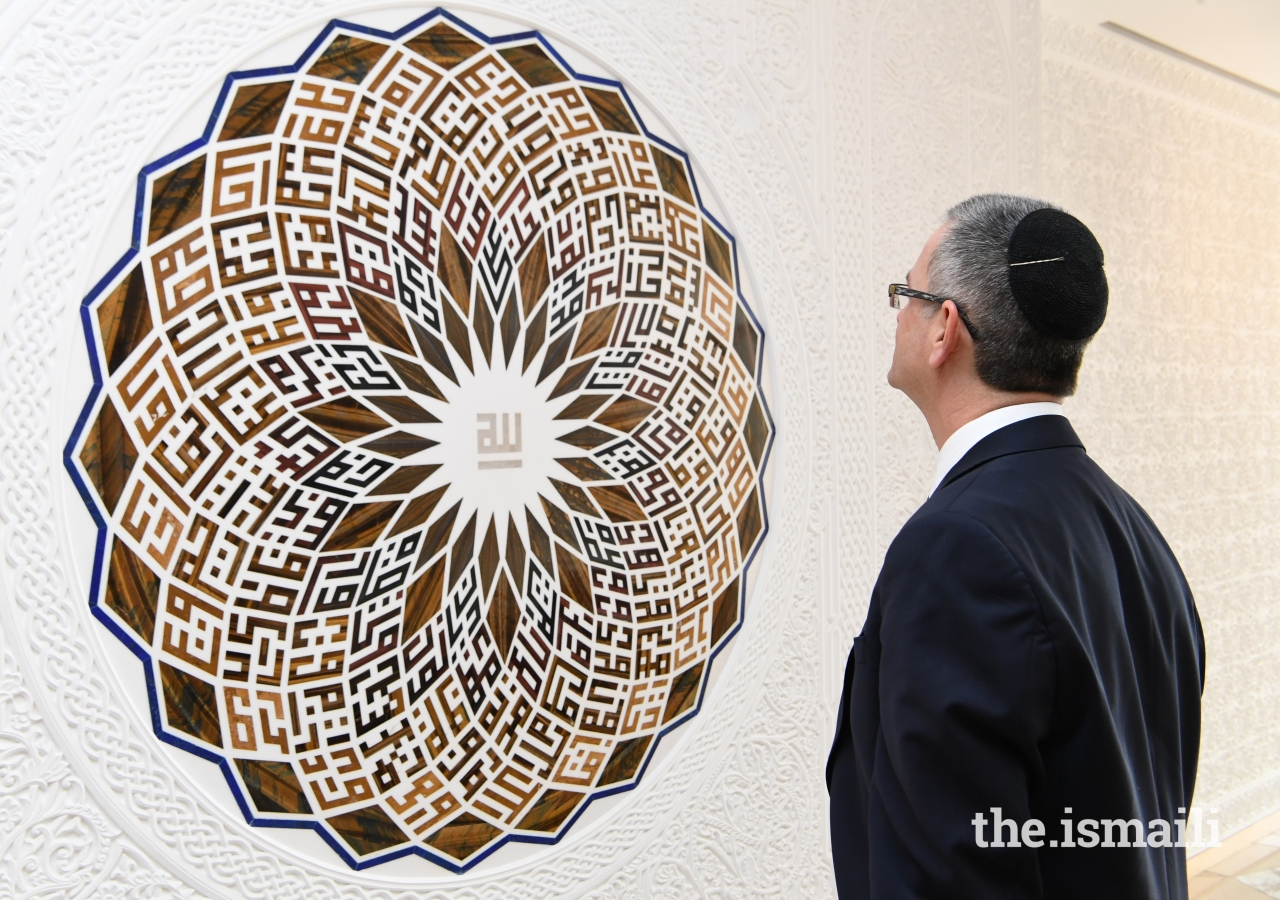 "Senior Rabbi of Leo Baeck Temple in Los Angeles, Ken Chasen, admires the ""99 Names of Allah"" artwork by Minaz Nanji, at the Ismaili Centre, Toronto."