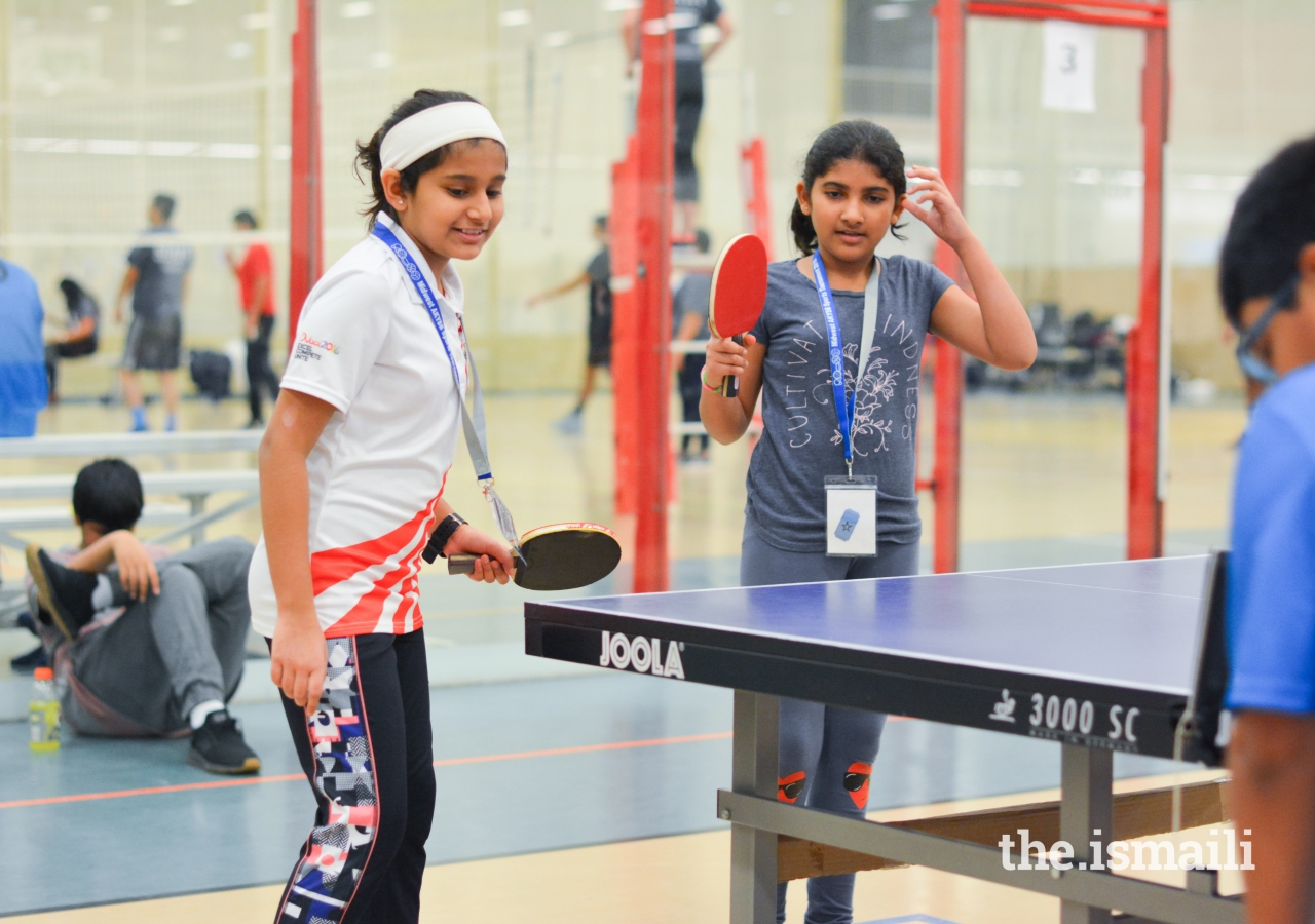 Doubles partners Arzoo Rozani and Zaina Jawaid wait for their opponents to return the ball.