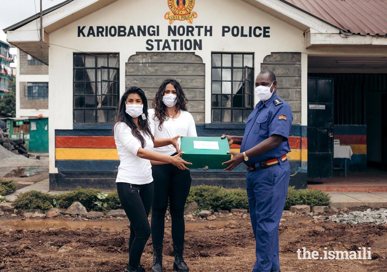Alisha Popat and Talisa Lanoe present a box of masks to a representative from the Kariobangi North Police Station as part of their #TasksForMasks campaign.