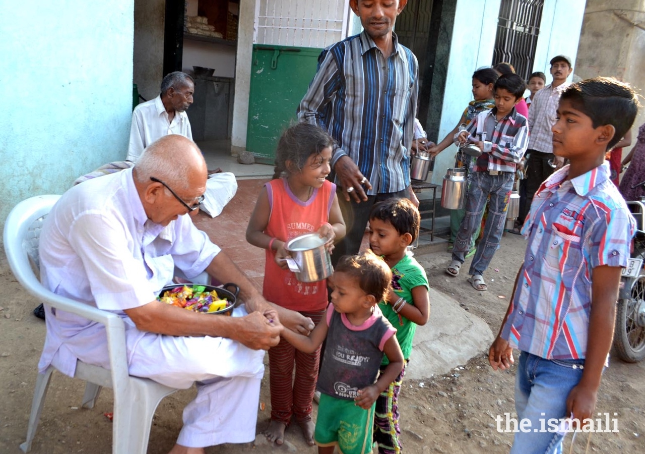 Amirbhai Lalani distributes sweets to disadvantaged children in Northern Saurashtra, India.