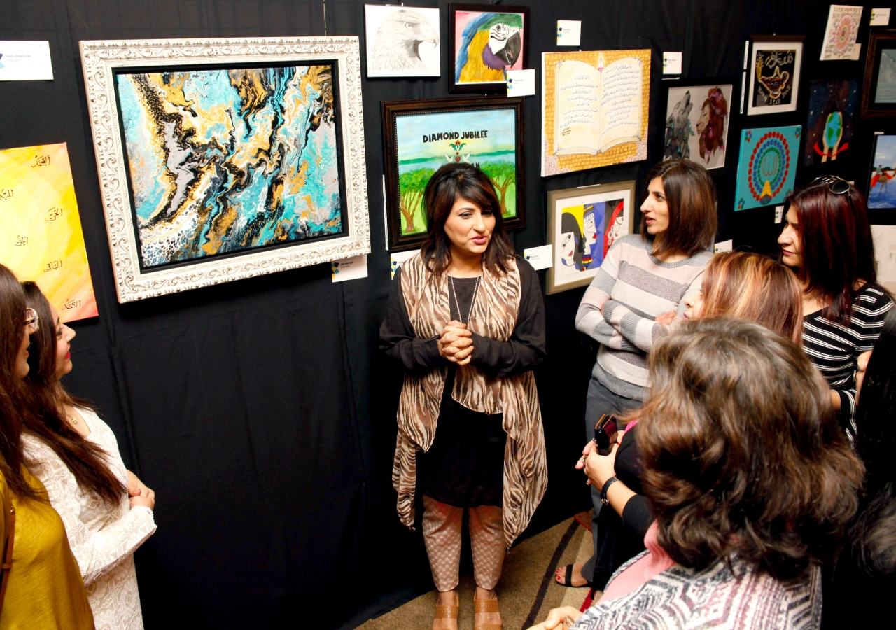 Attendees listen intently as Samina Hooda talks about the techniques and inspiration behind her work of art