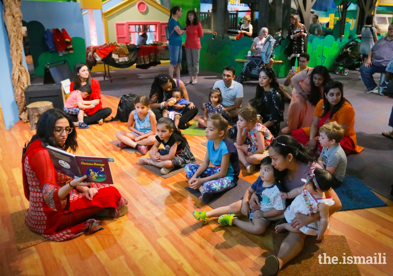 Laila Aziz reads stories to children at the Atlanta Children's Museum during the Meet the Holidays celebration.