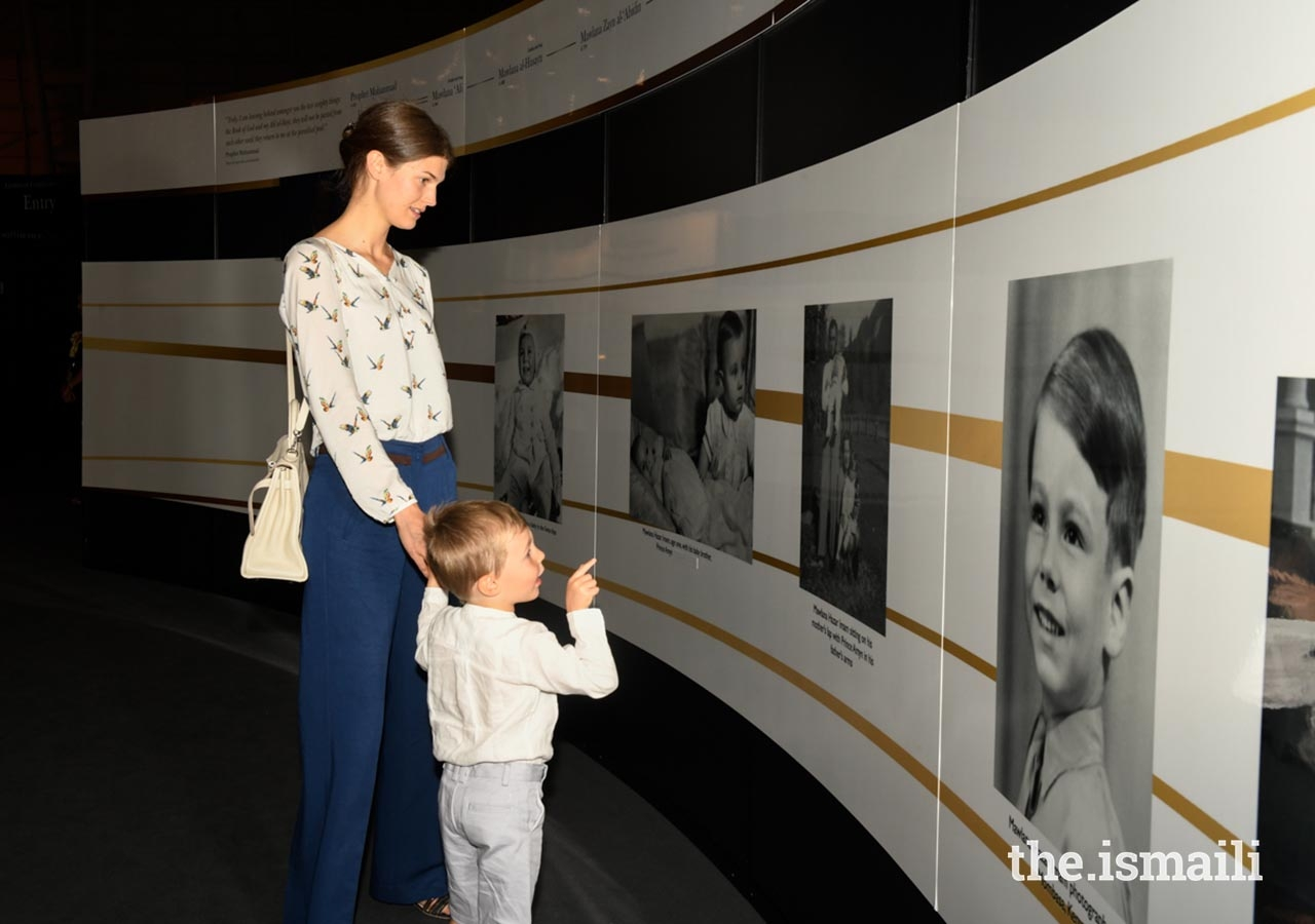 Princess Salwa shows Prince Irfan a picture of Mawlana Hazar Imam as a young boy at the Rays of Light exhibition in Lisbon.