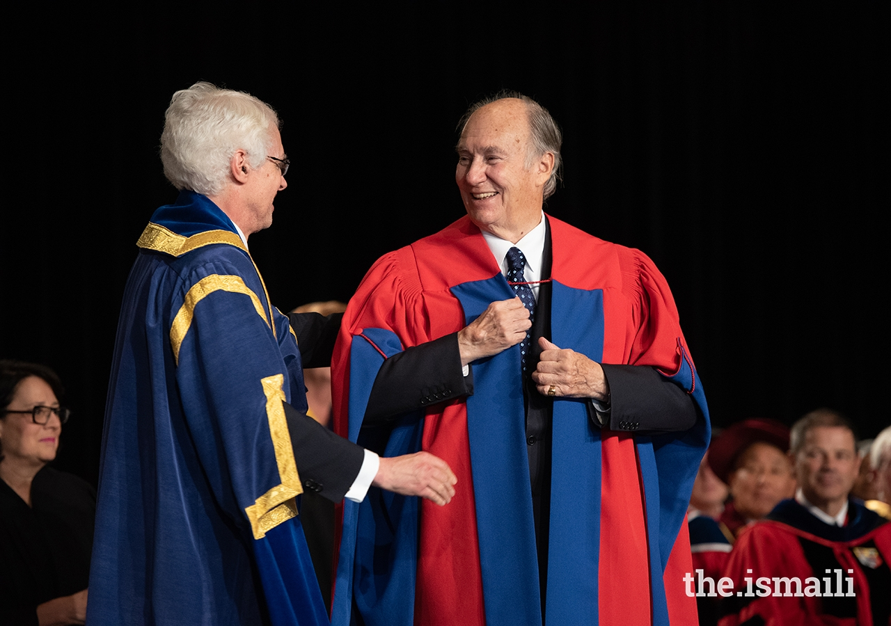 SFU President and Vice-Chancellor Andrew Petter adjusts the ceremonial SFU robe on Mawlana Hazar Imam as part of honorary degree conferral ceremony.