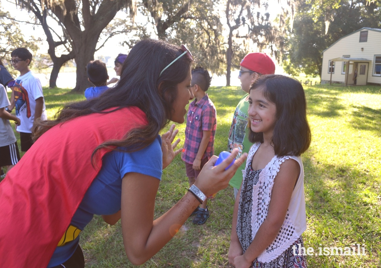 On Superhero day, a counselor engages with her participant one-on-one during sports.