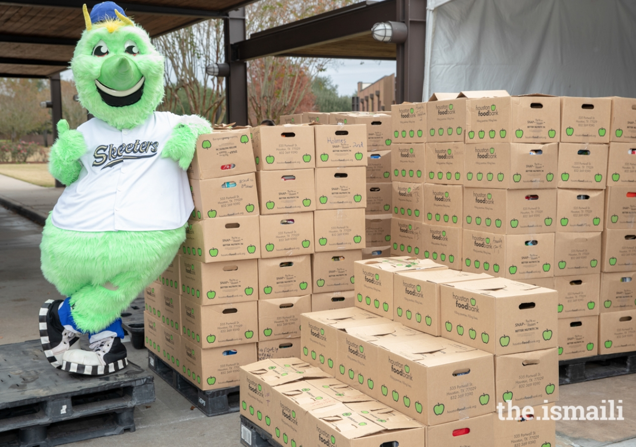 Swatson, mascot of the Sugar Land Skeeters, posing next to a few of the donated food items., Over 30,000 pounds of food were collected at the Ismaili Jamatkhana and Center and donated to the East Fort Bend Human Needs Ministry in Stafford, Texas.