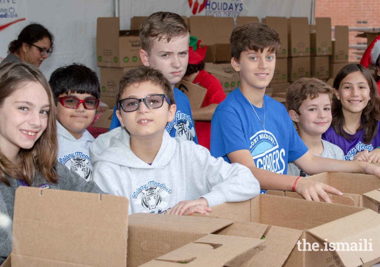 Several students who participated in the Share Your Holidays Food Drive helped package donated items.