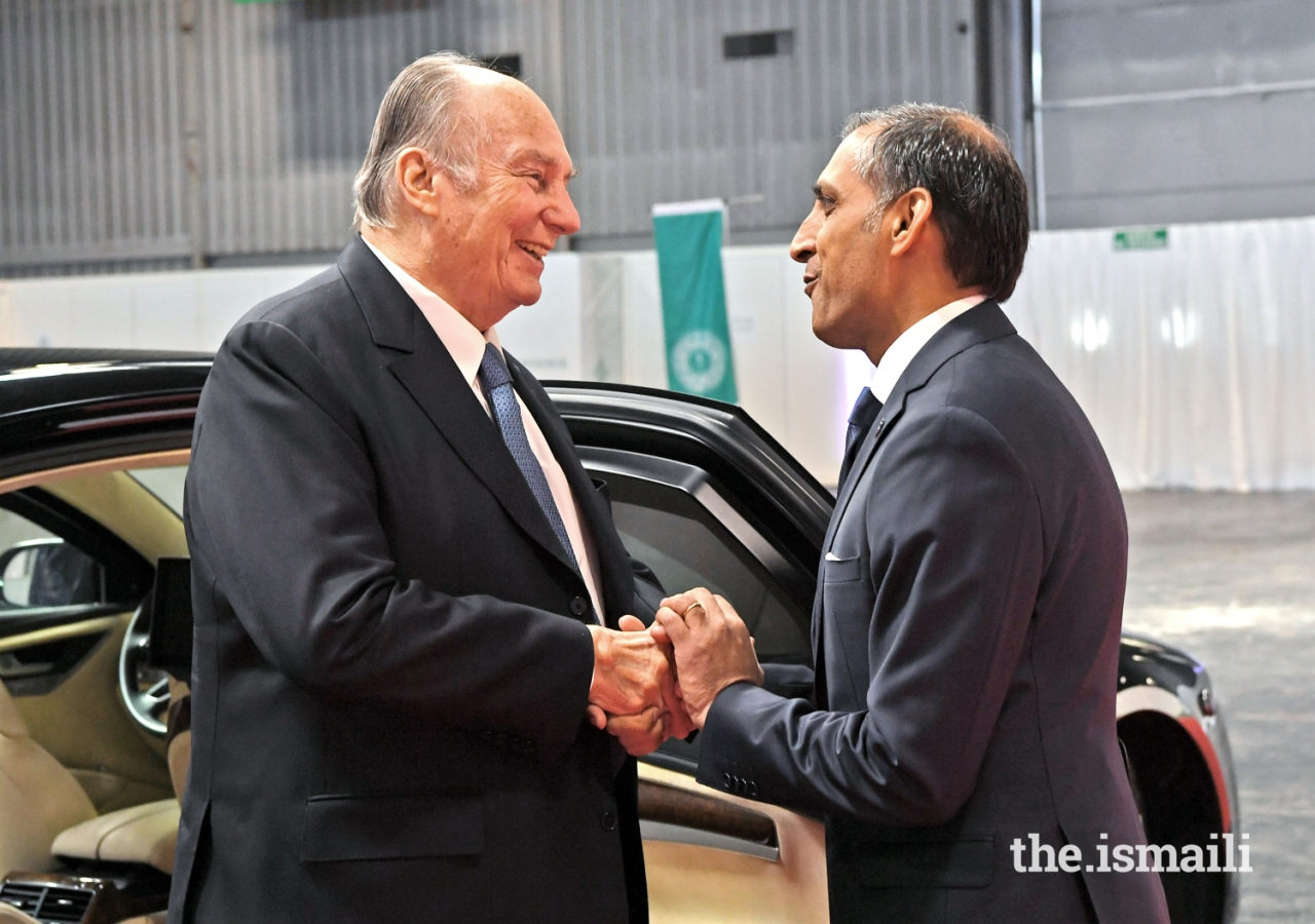 Upon arriving to meet the Jamat, Mawlana Hazar Imam is welcomed by Ismaili Council for France President Shamir Samdjee.