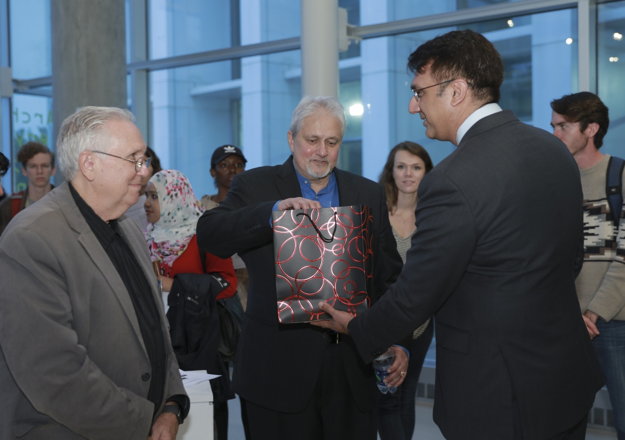 President Murad Abdullah of the Ismaili Council for the Southeast presenting Prof. Khan with a gift, as Prof. Cole looks on.