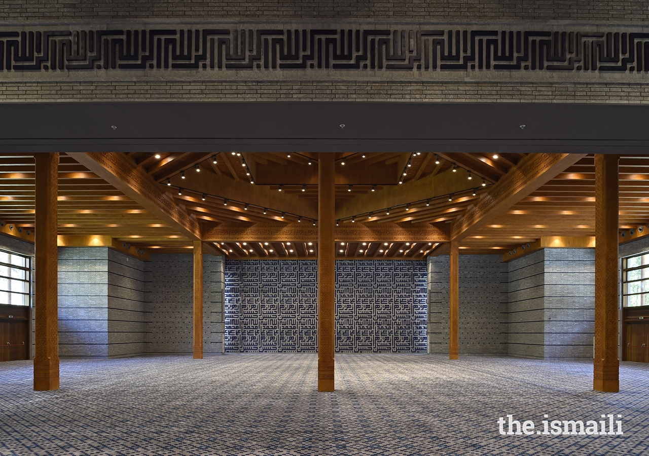 The prayer hall of the Ismaili Jamatkhana and Centre, Khorog. The geometric Kufic script at the wall articulates the names of the Ahl al-Bayt, or House of the Prophet.