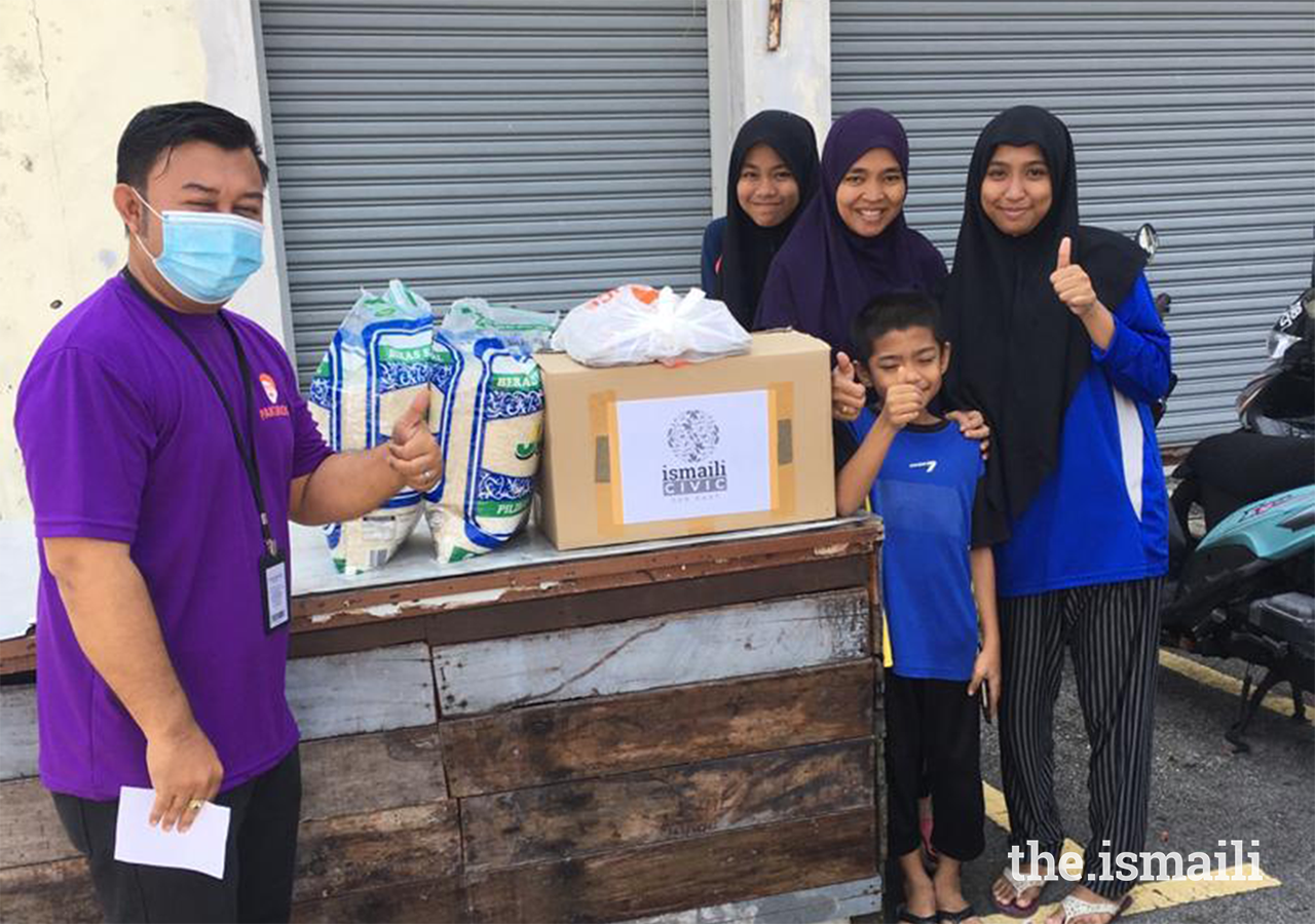 A volunteer delivers a care package to a family as part of the partnership programme between Ismaili CIVIC and Yayasan Chow Kit in Malaysia.