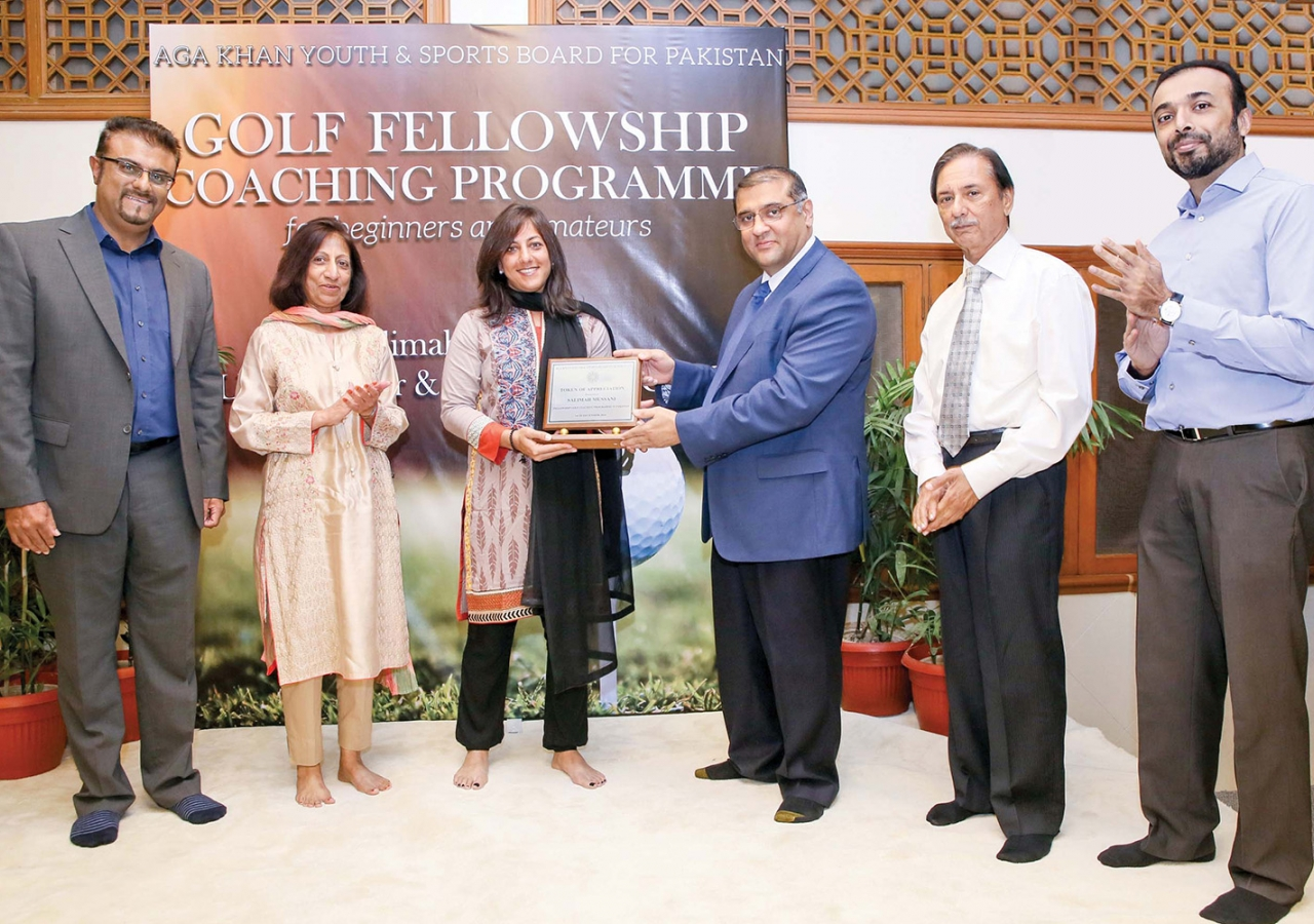 Hafiz Sherali, President of the Ismaili Council for Pakistan presents a memento to golf coach Salimah Mussani.